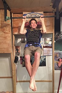 The author doing weighted pull-ups (75lb of added weight).